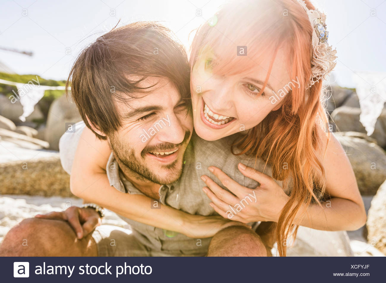 Woman behind man arms around shoulders smiling - Stock Image