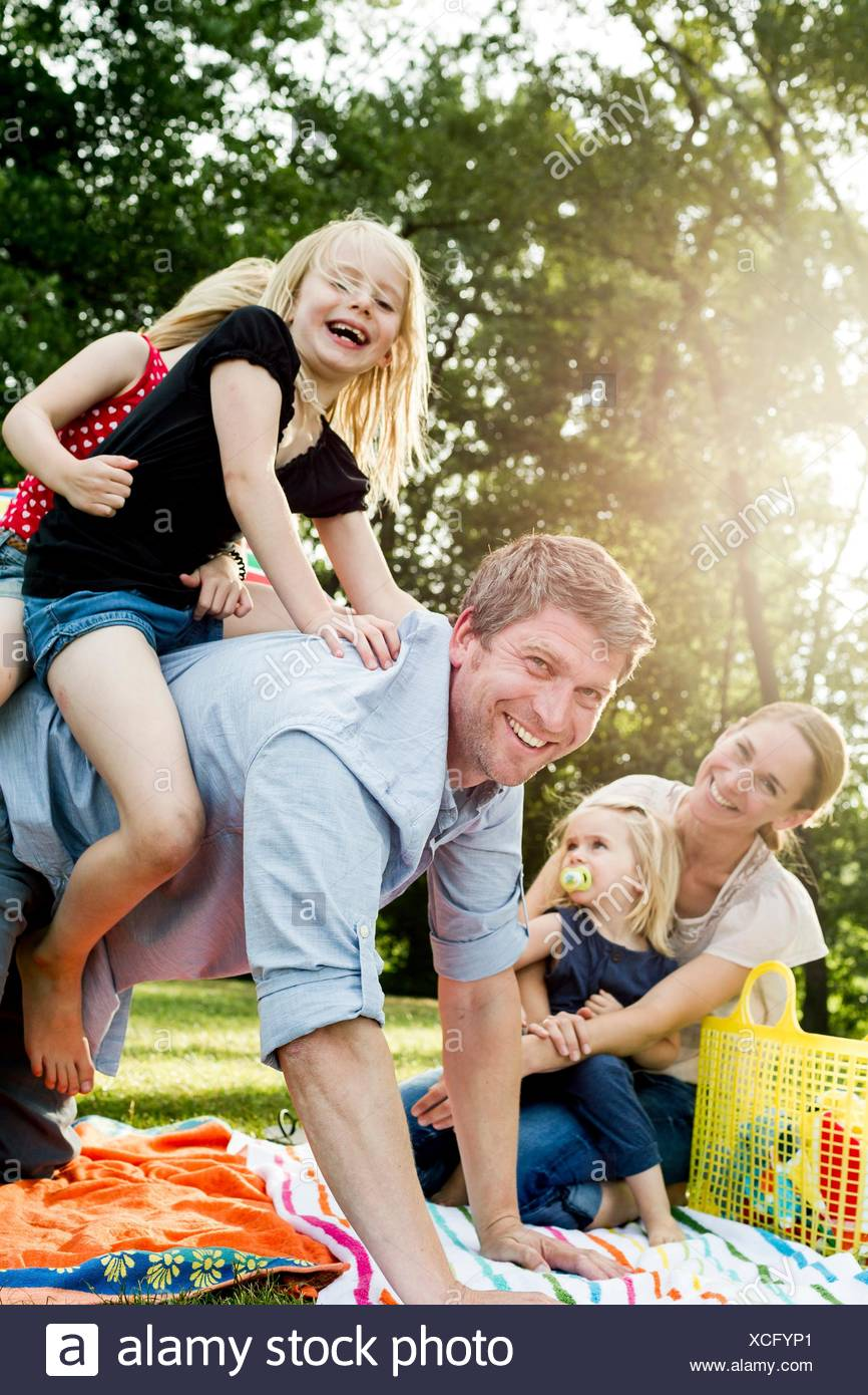 Father giving daughters piggyback at family picnic in park - Stock Image