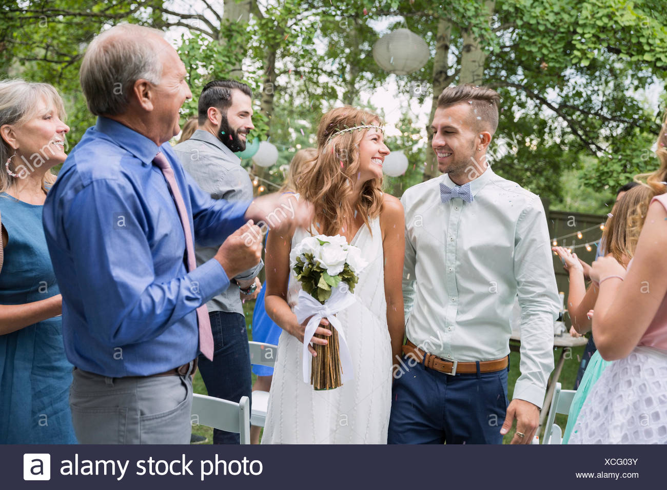 Guests clapping for bride and groom backyard wedding - Stock Image