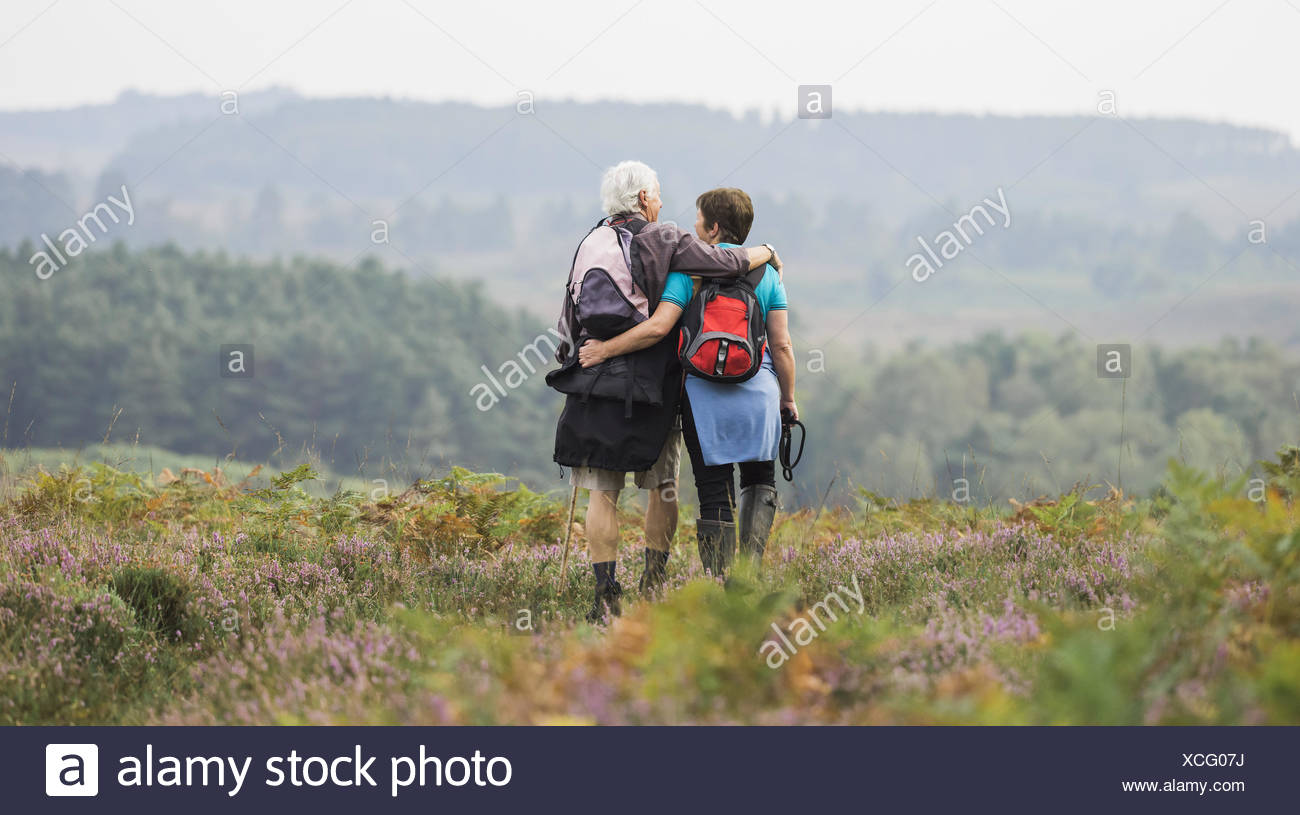 A couple standing on a path looking at the view over wooded hills, with arms around each other. - Stock Image