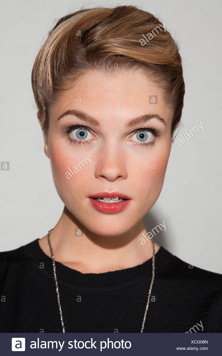 Portrait of a beautiful woman looking surprised - Stock Image
