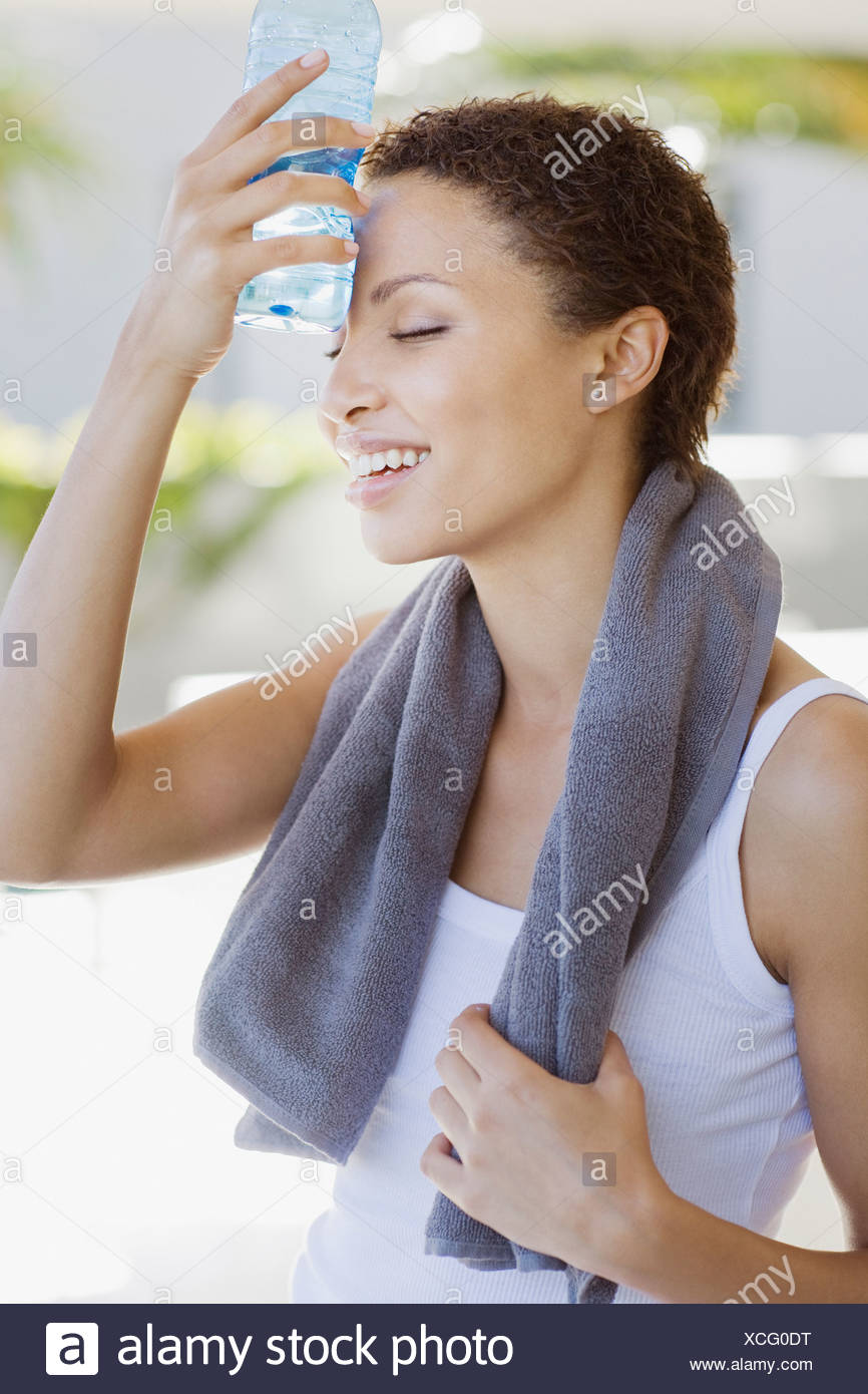 Tired woman cooling off with water bottle - Stock Image