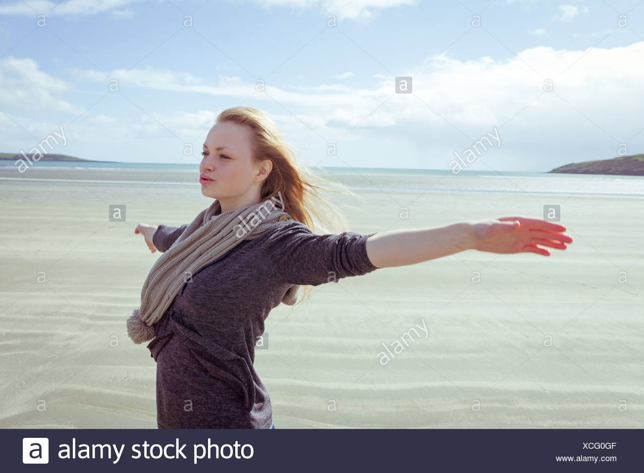 Attractive woman opening her arms in front of the ocean - Stock Image