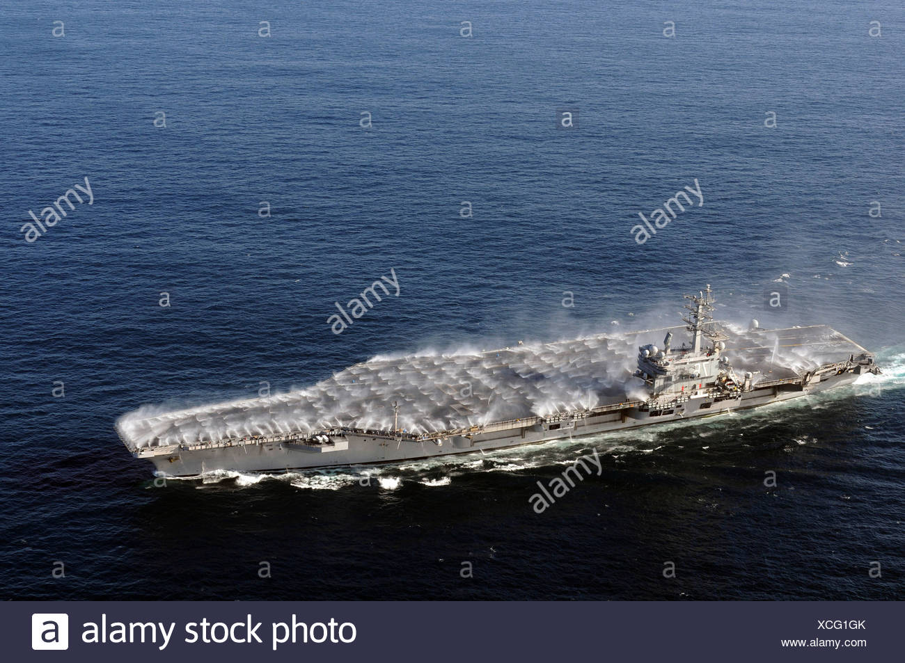 Countermeasure wash down sprinklers are activated as the Nimitz-class aircraft carrier USS Ronald Reagan (CVN-76) transits - Stock Image