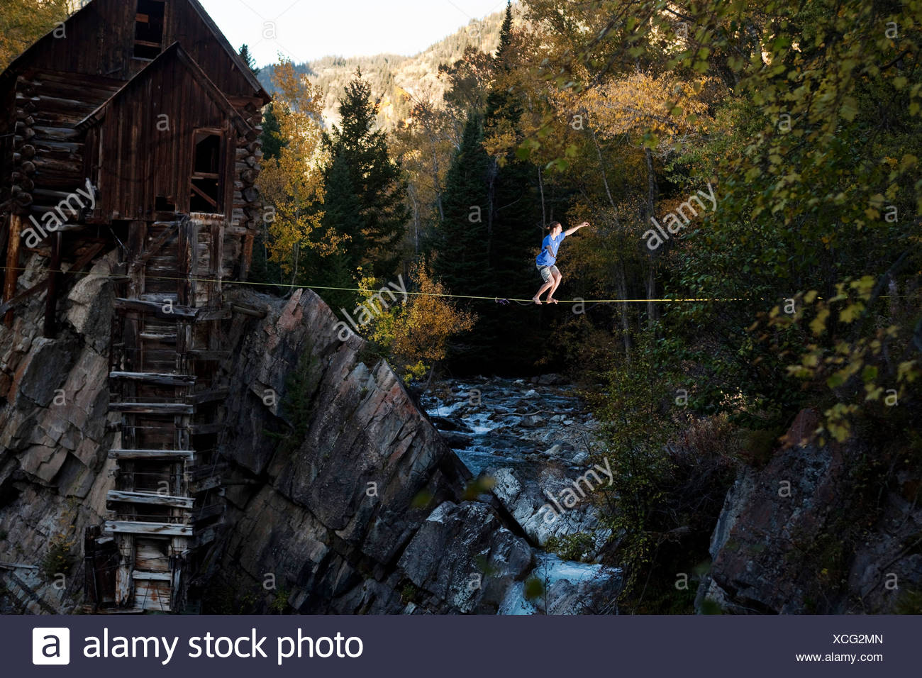 A young man walks a high line with glowing leaves and a raging river below. - Stock Image