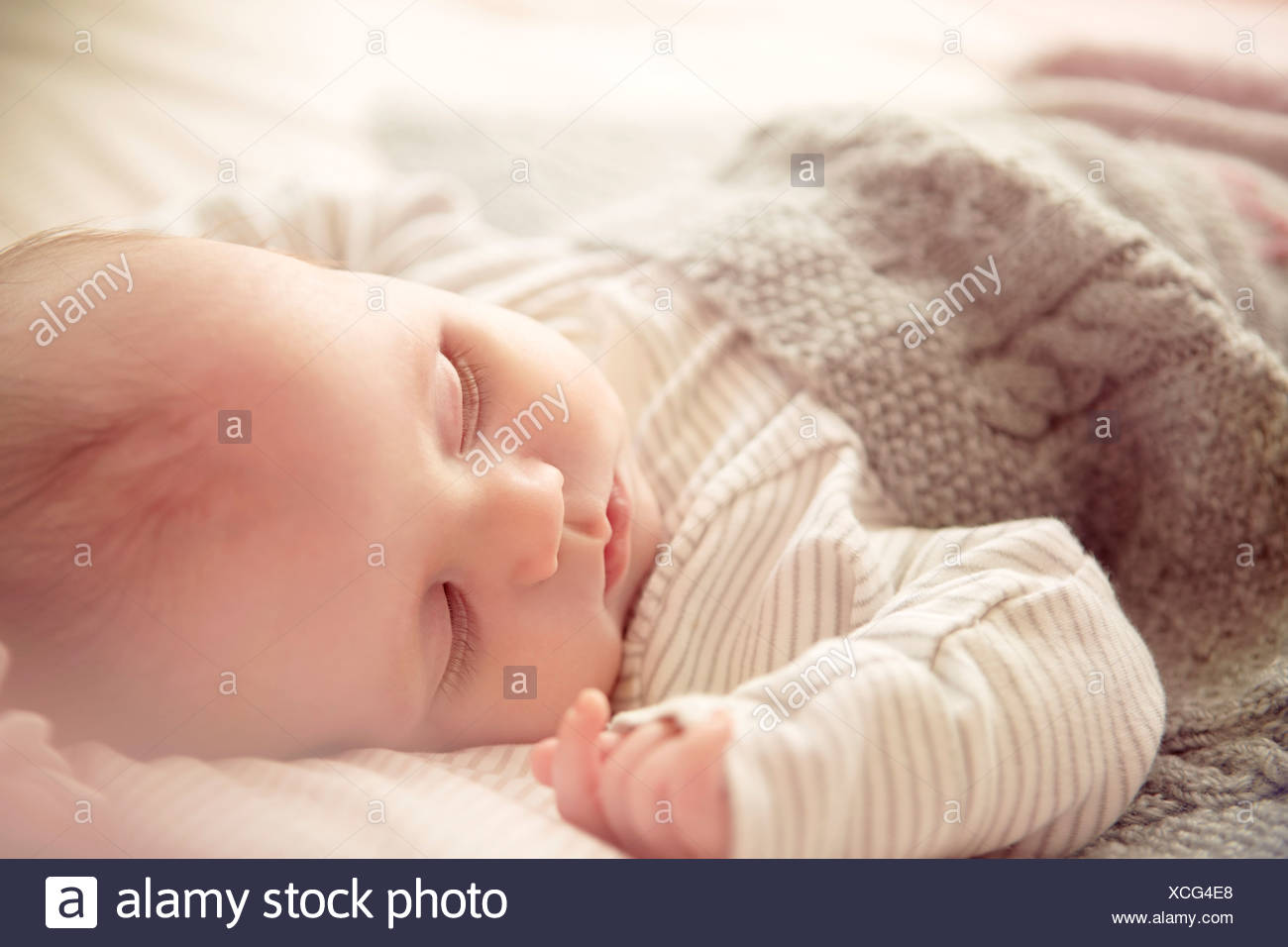 Two month old baby boy asleep in crib - Stock Image