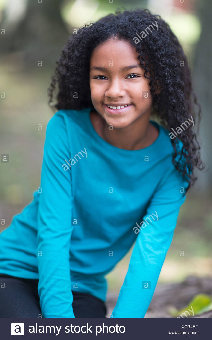 Portrait of happy young girl in park - Stock Image