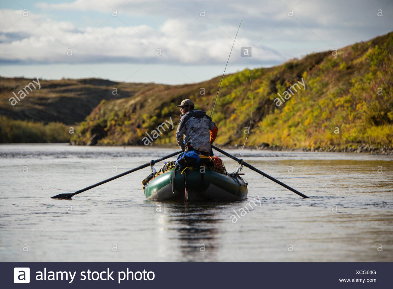 A man scans the water for salmon while rowing his raft down an unnamed creek in western Alaska. - Stock Image
