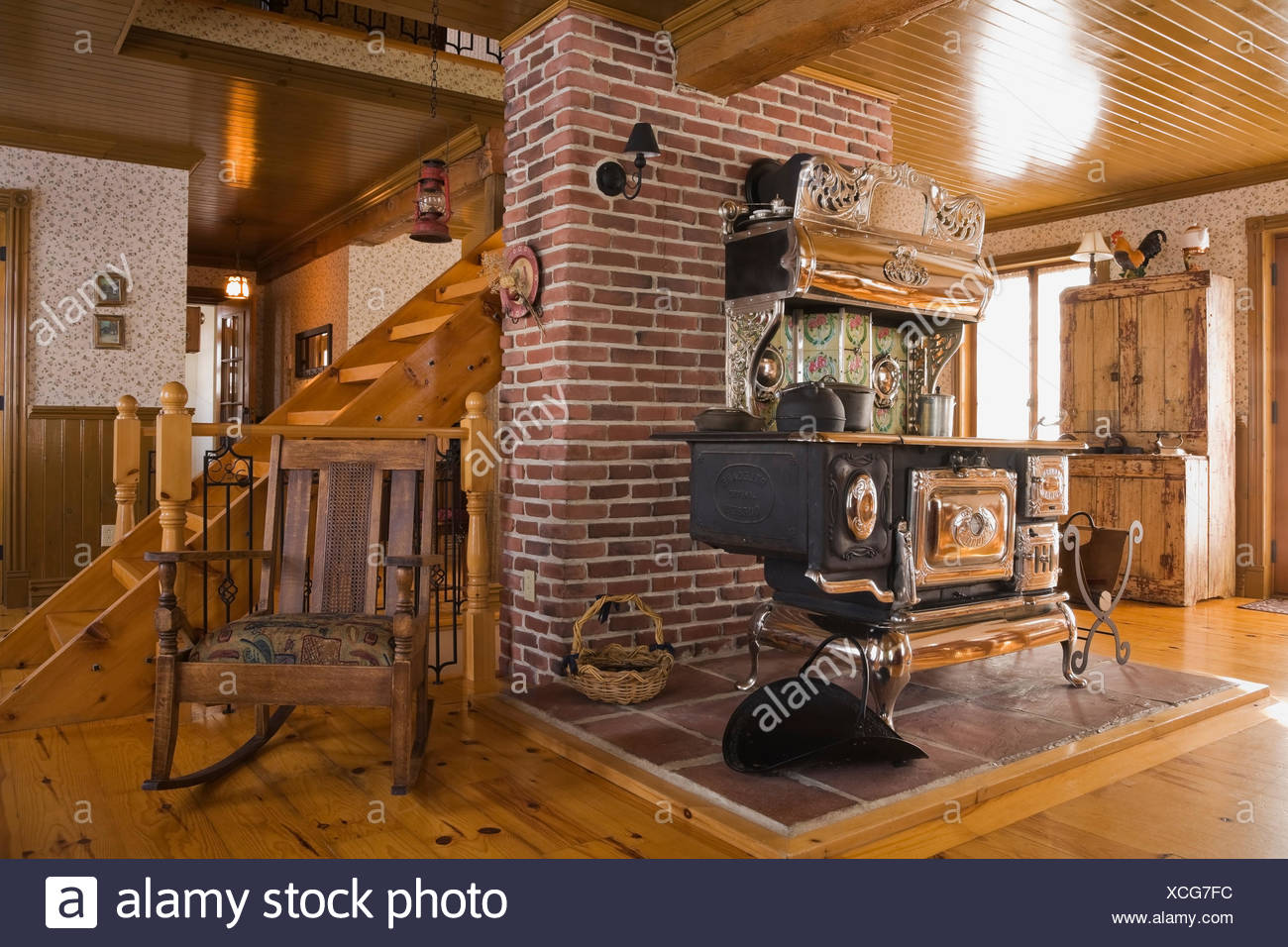 Old Legare's Rural antique wood stove in the living room a Canadiana cottage style fieldstone residential home built to look - Stock Image