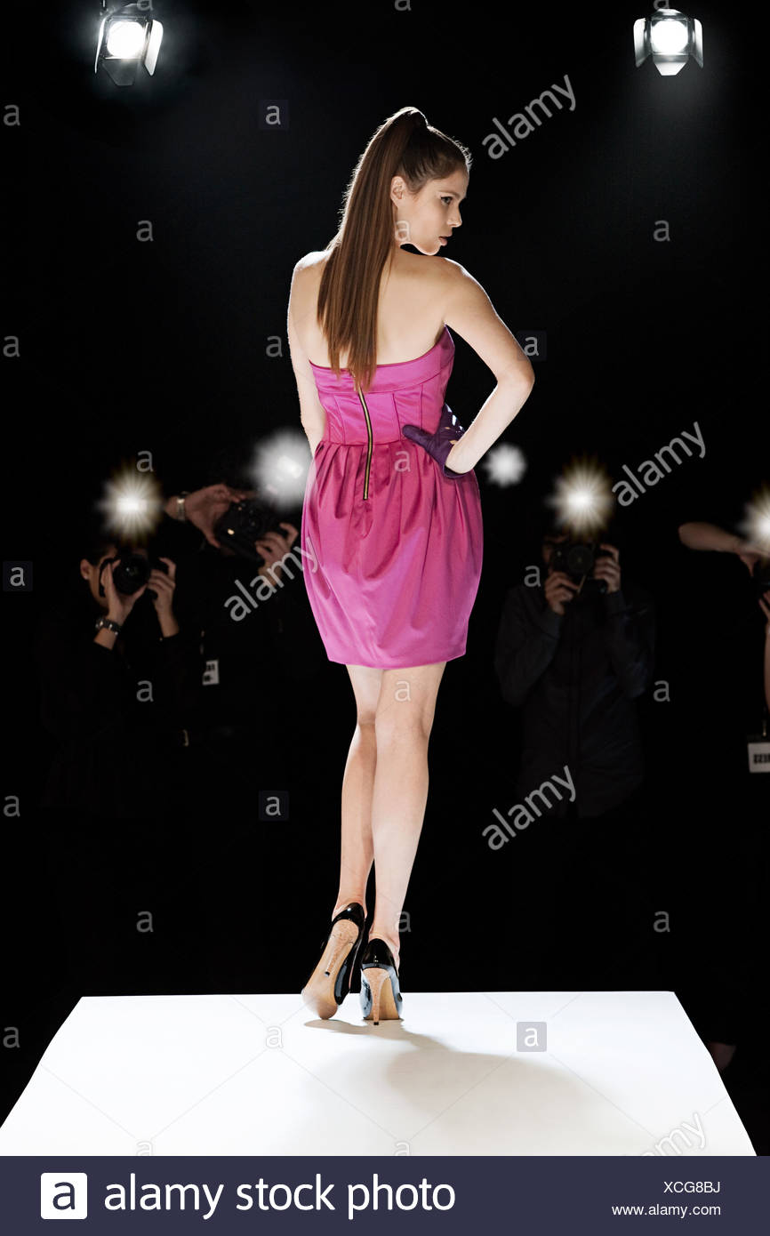 Model being photographed on catwalk at fashion show - Stock Image