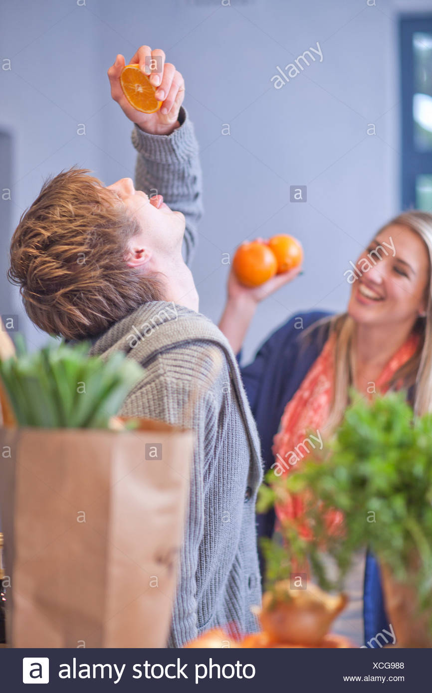 Young couple messing around in kitchen - Stock Image