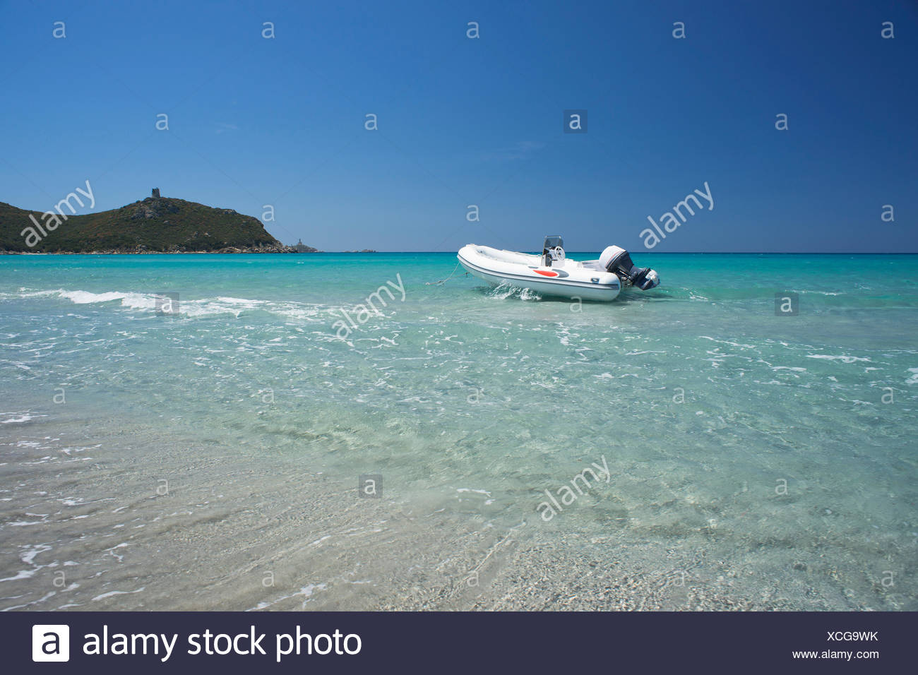 A rubber dinghy anchored in front of the ruins of the Saracen tower on the beach of Cala Porto Giunco, Capo Cabonara - Stock Image