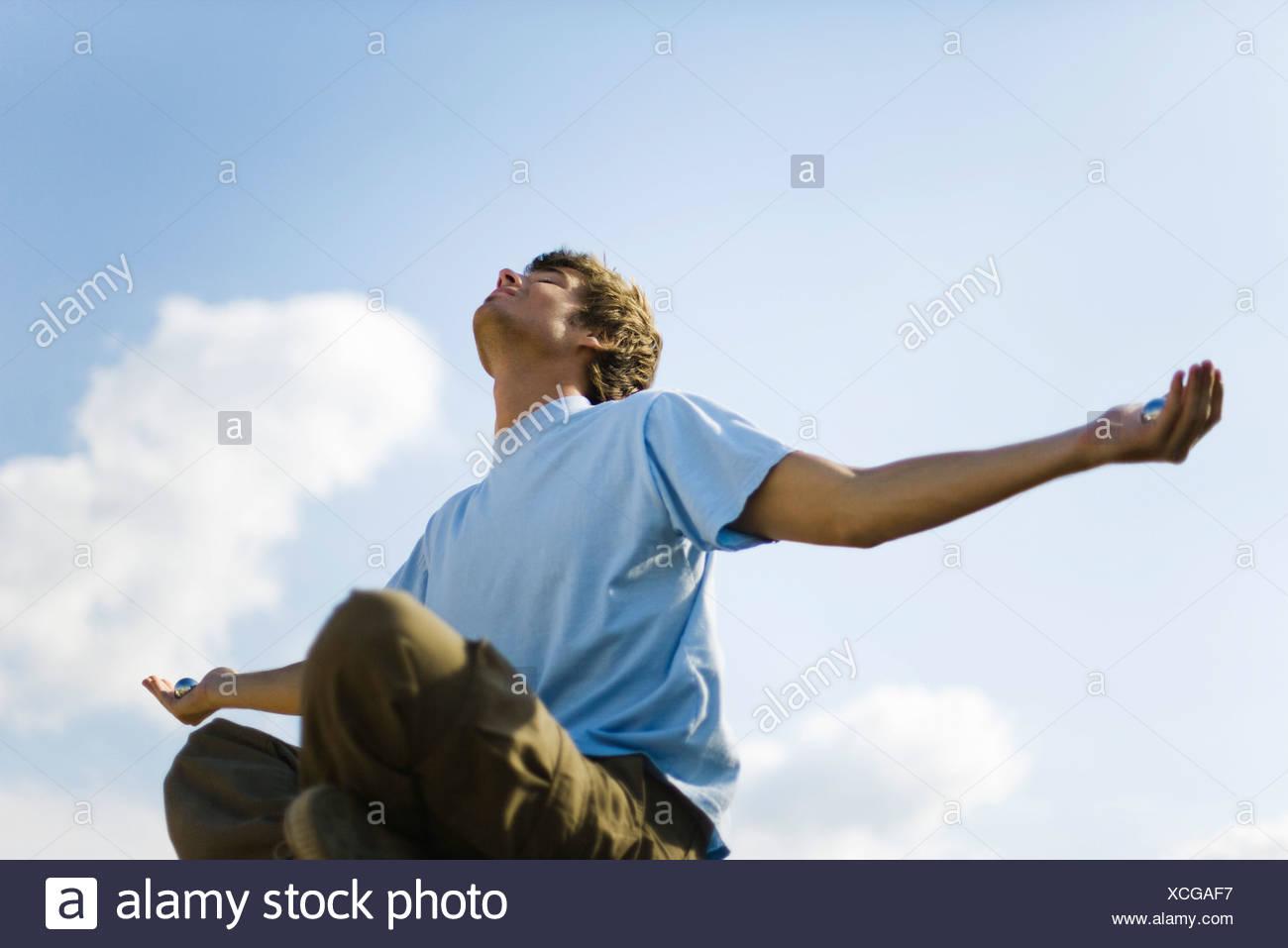 Young man meditating outdoors, holding yin yang balls - Stock Image