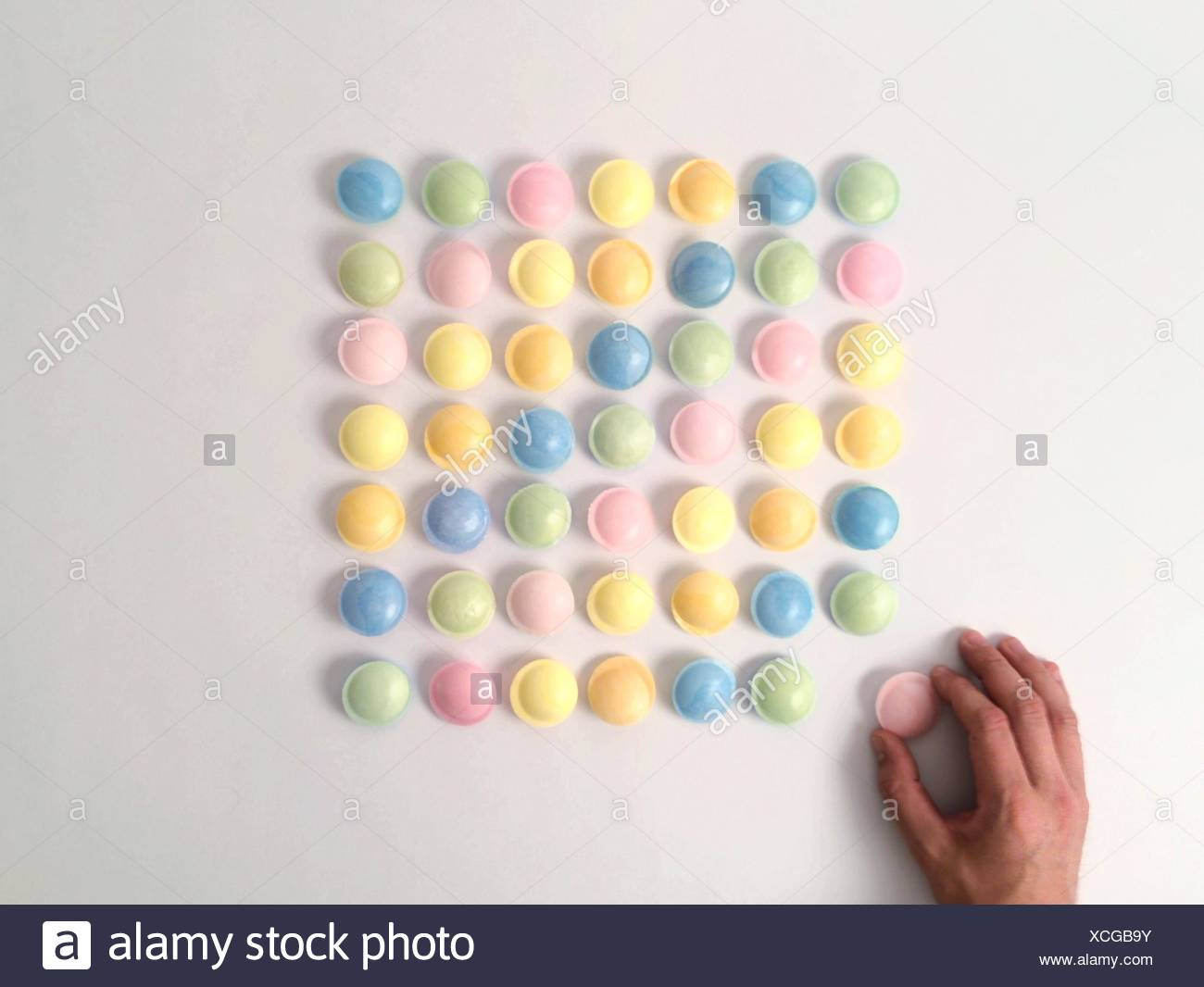 Directly Above View Of Person Arranging Candies Against White Background - Stock Image