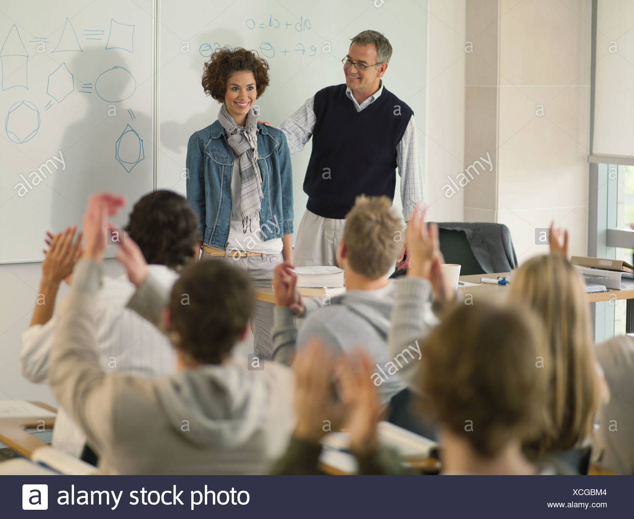 Professor and college student at front of classroom - Stock Image