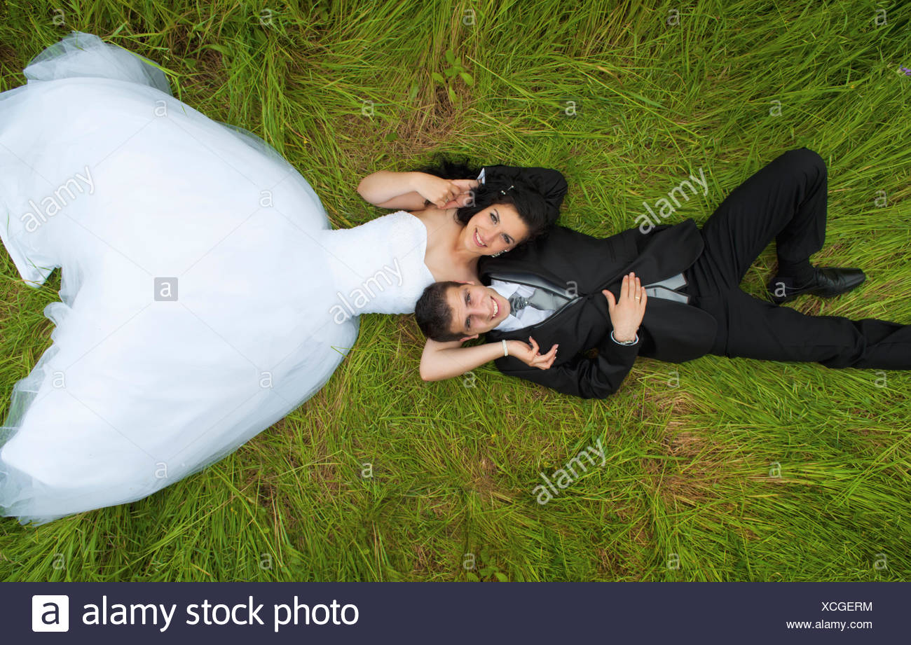 Bride and groom lying on grass - Stock Image