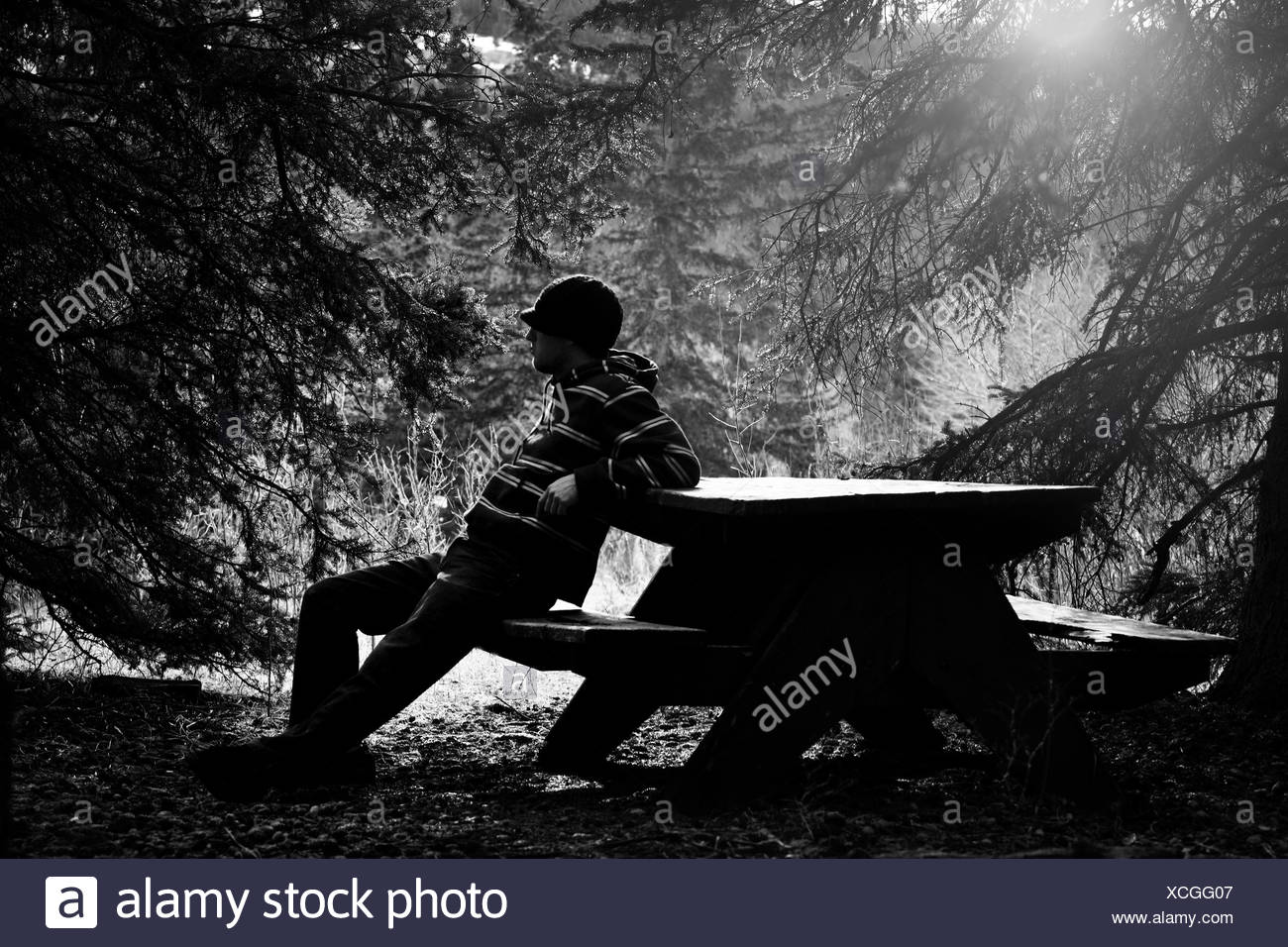 Man sitting; Man resting on picnic table - Stock Image