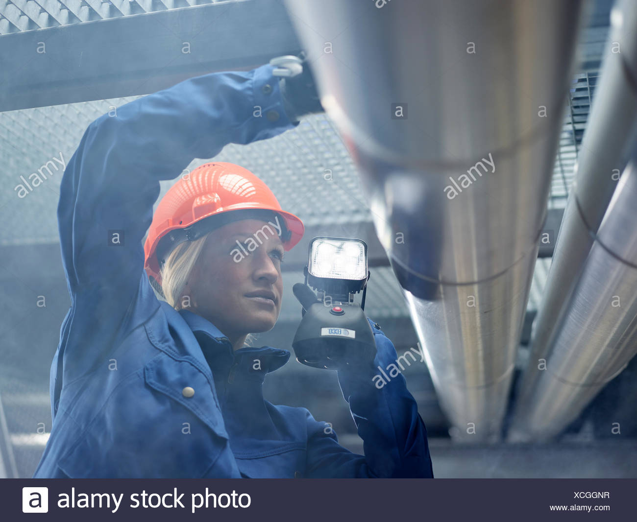 Technician, fitter with orange helmet and lamp inspected pipelines, Wattens, Tyrol, Austria - Stock Image