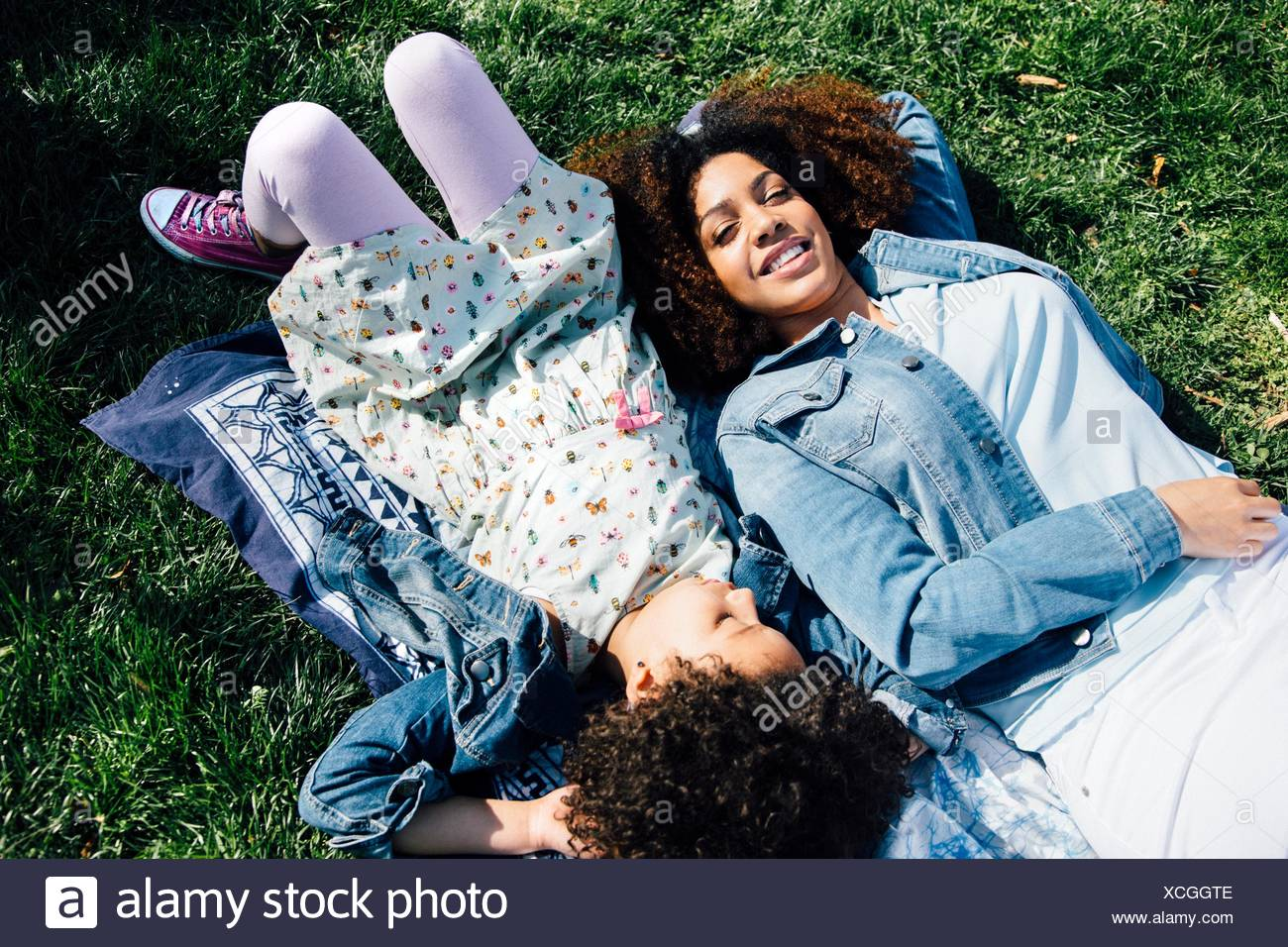 High angle view of mother and daughter lying side by side on backs, eyes closed - Stock Image