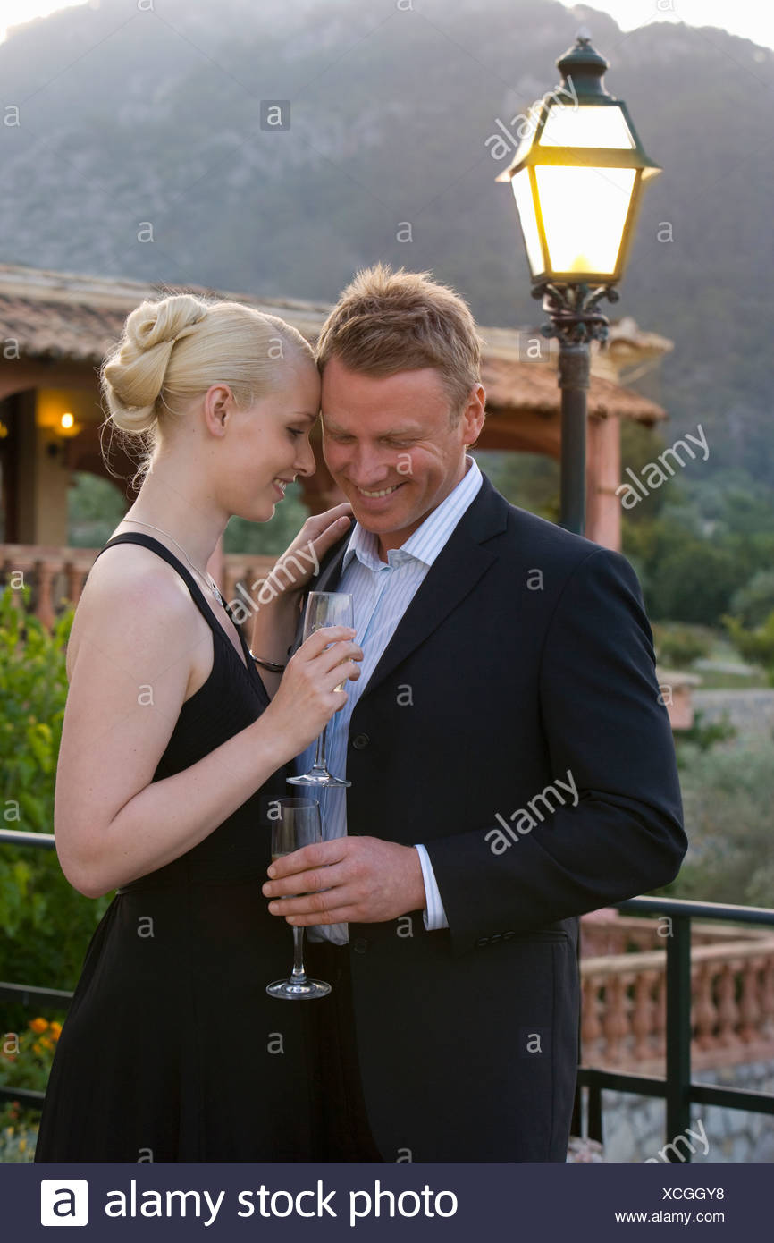 Well-dressed couple hugging and drinking champagne on balcony - Stock Image