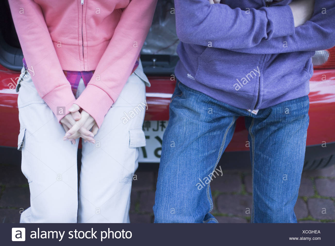 Young Couple Sitting on Vehicle Trunk,low section - Stock Image