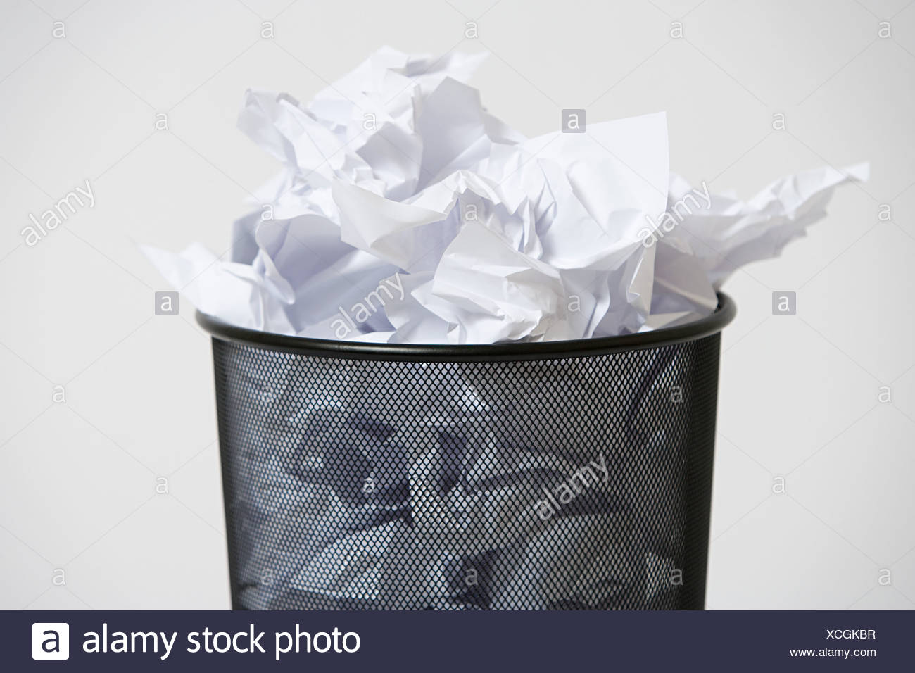 A wastepaper basket with crumpled up paper in it - Stock Image