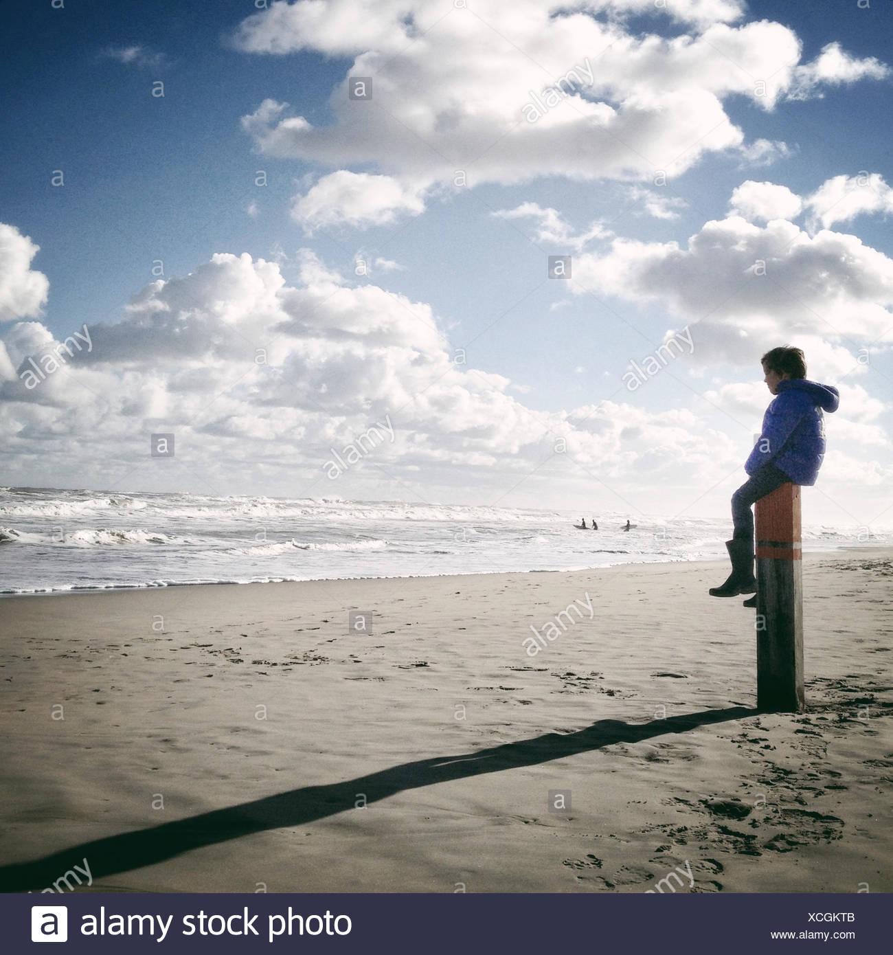 Boy sitting on wooden post on beach - Stock Image