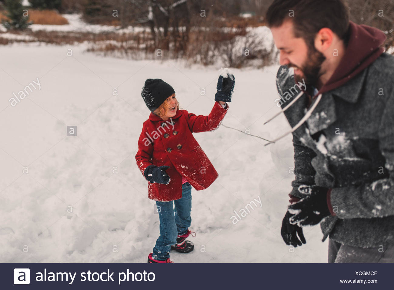 Girl throwing snowball at her father - Stock Image