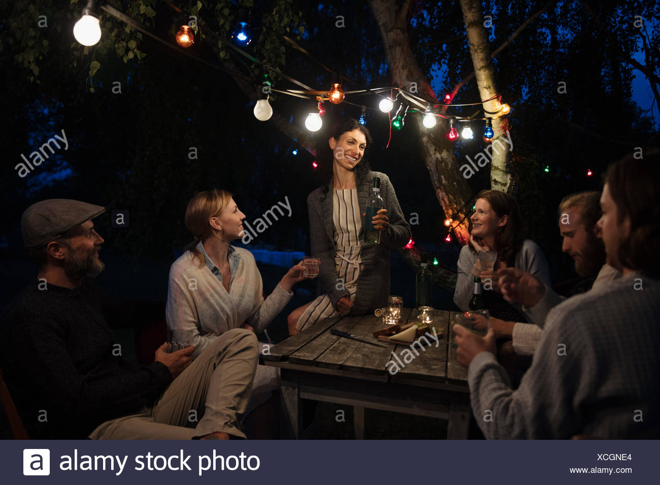 Friends drinking and toasting under string lights at dark garden party - Stock Image