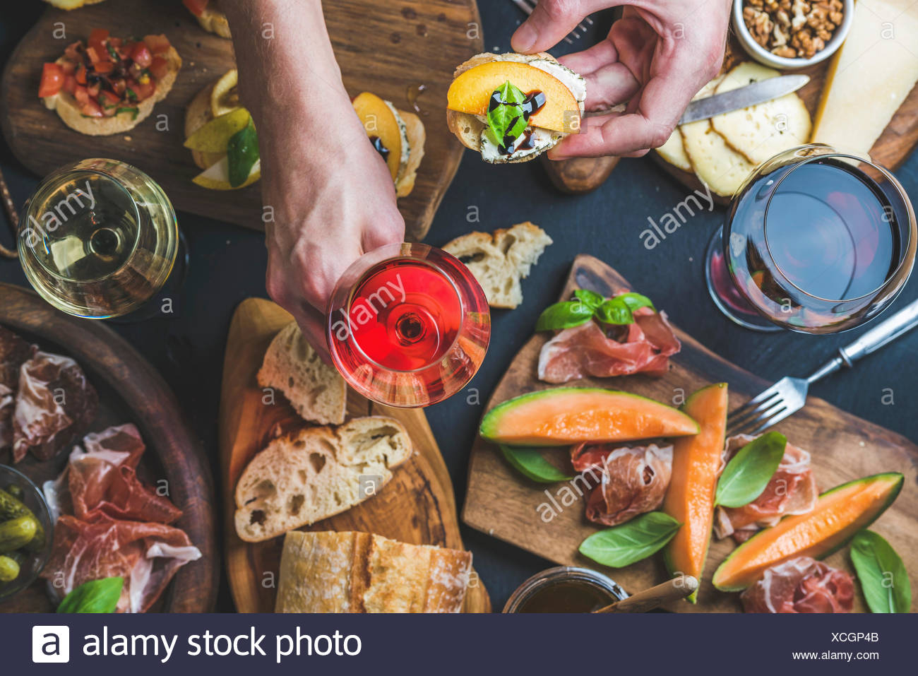 Italian wine antipasti snack variety and man's hands holding glass of rose wine and bruschetta, top view, selective focus - Stock Image