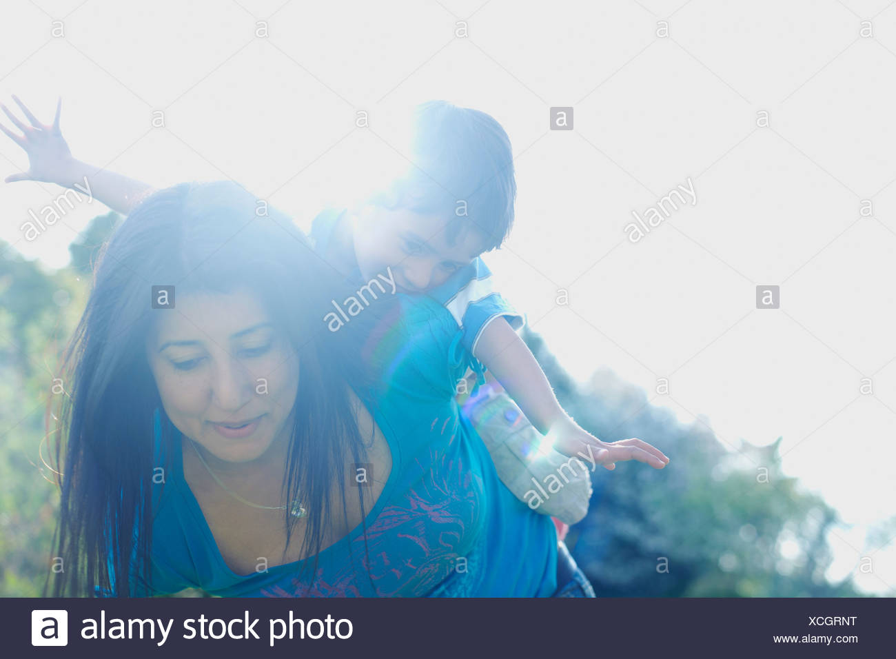 Boy riding on mother's back with arms stretched out - Stock Image
