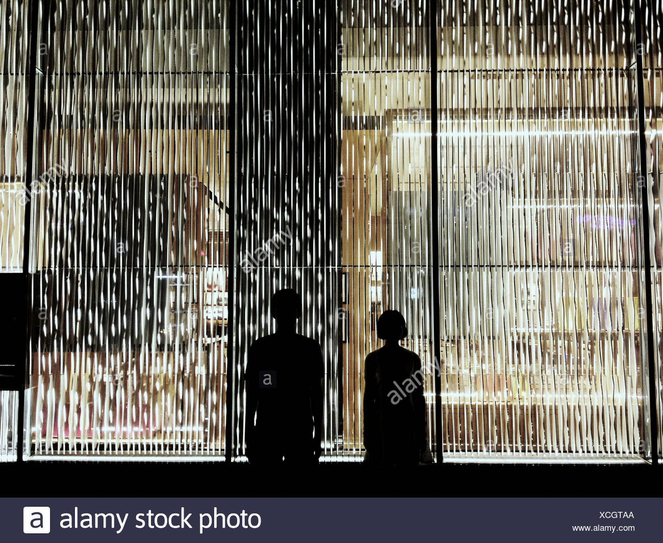 Silhouette Couple Standing Against Window With Blinds - Stock Image
