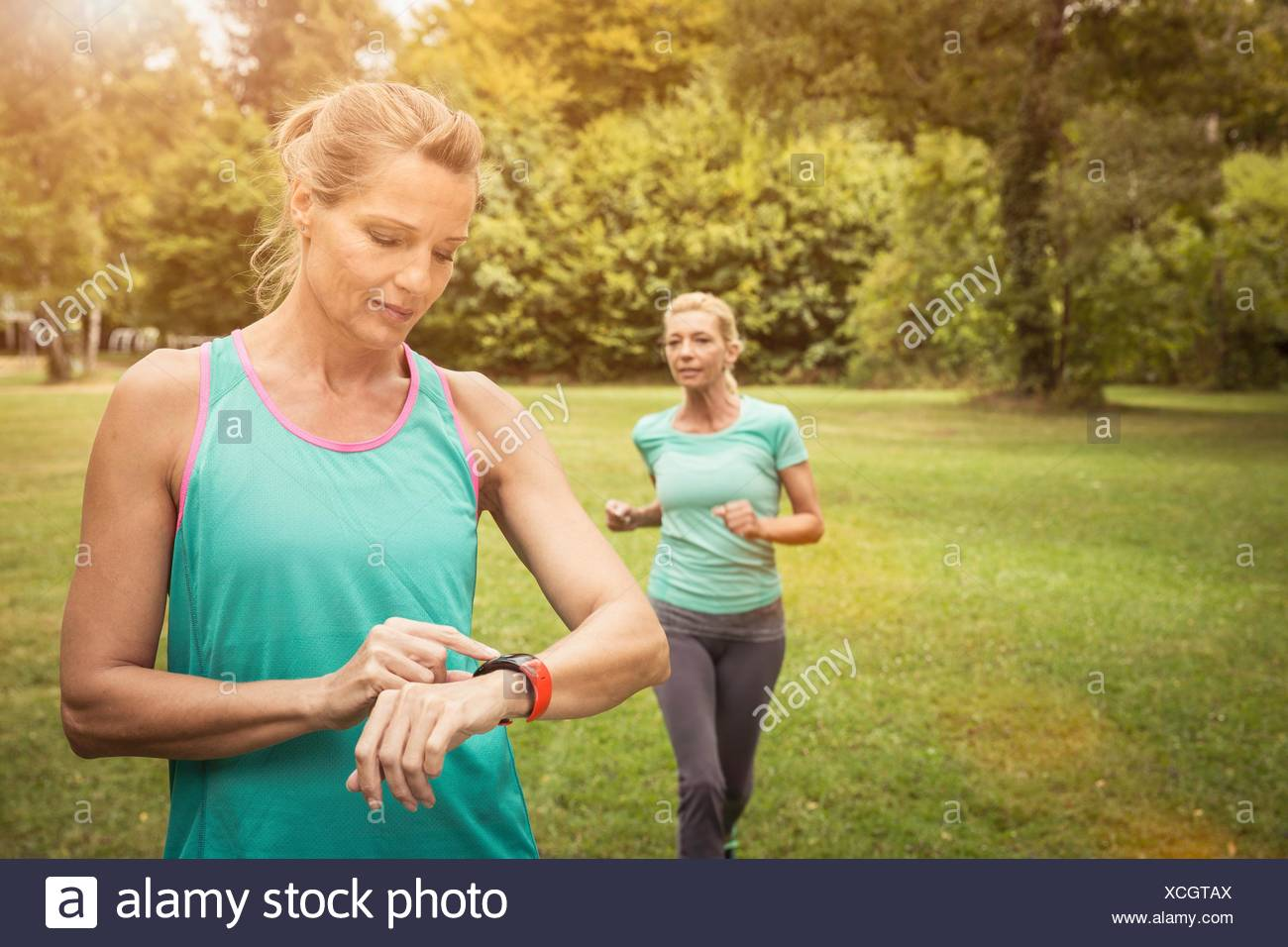 Mature women jogging in park, checking heart rate monitor wrist watch - Stock Image