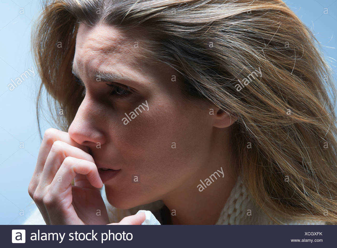 Close up of anxious woman with hand on mouth - Stock Image