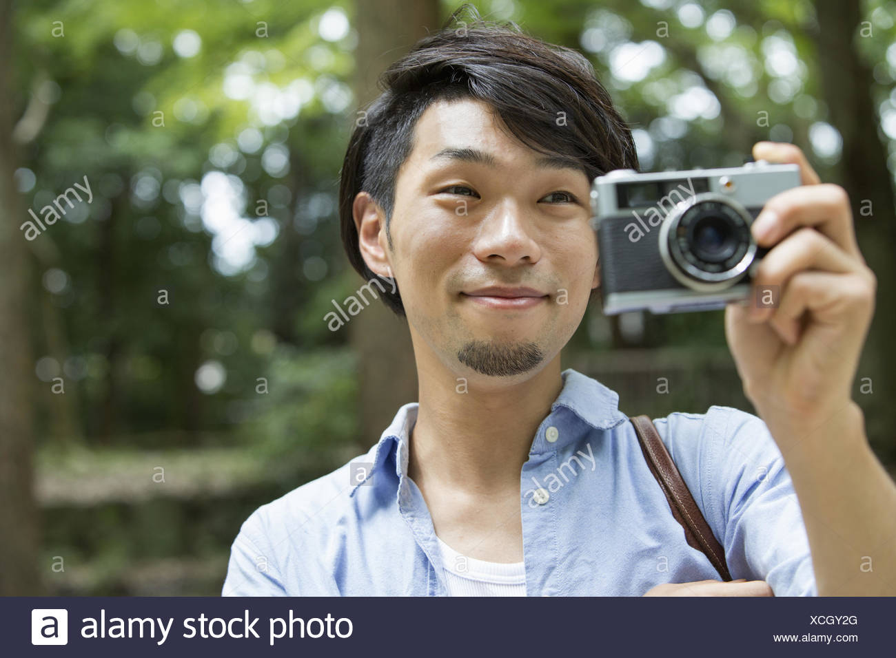 A man in a Kyoto park holding a camera, taking a picture. - Stock Image