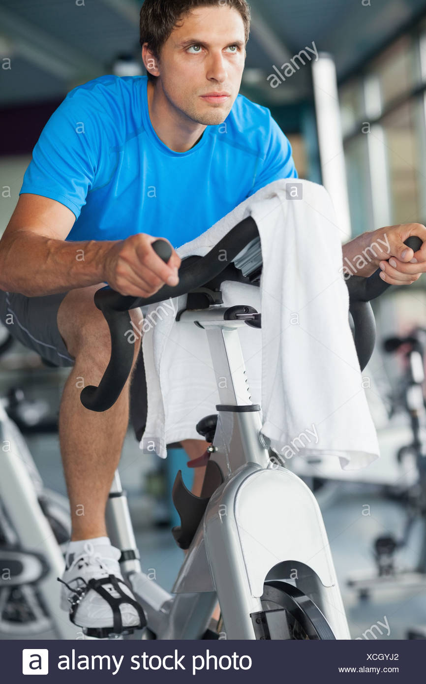 Determined man working out at spinning class Stock Photo