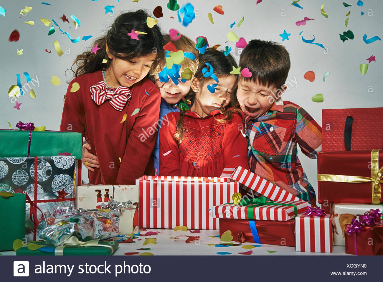 Surprised brothers and sisters unwrapping glowing christmas gift box with exploding confetti  sc 1 st  Alamy & Surprised brothers and sisters unwrapping glowing christmas gift box ...