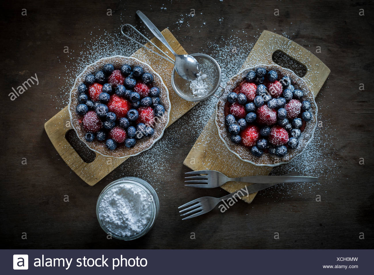 Berry tartetelets with icing sugar in baking dishes on wooden plates with sifter and cake forks. Top view - Stock Image