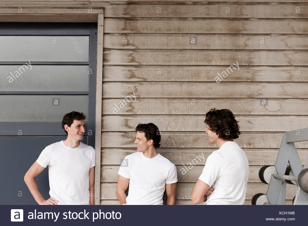 Men standing and chatting on front porch Stock Photo