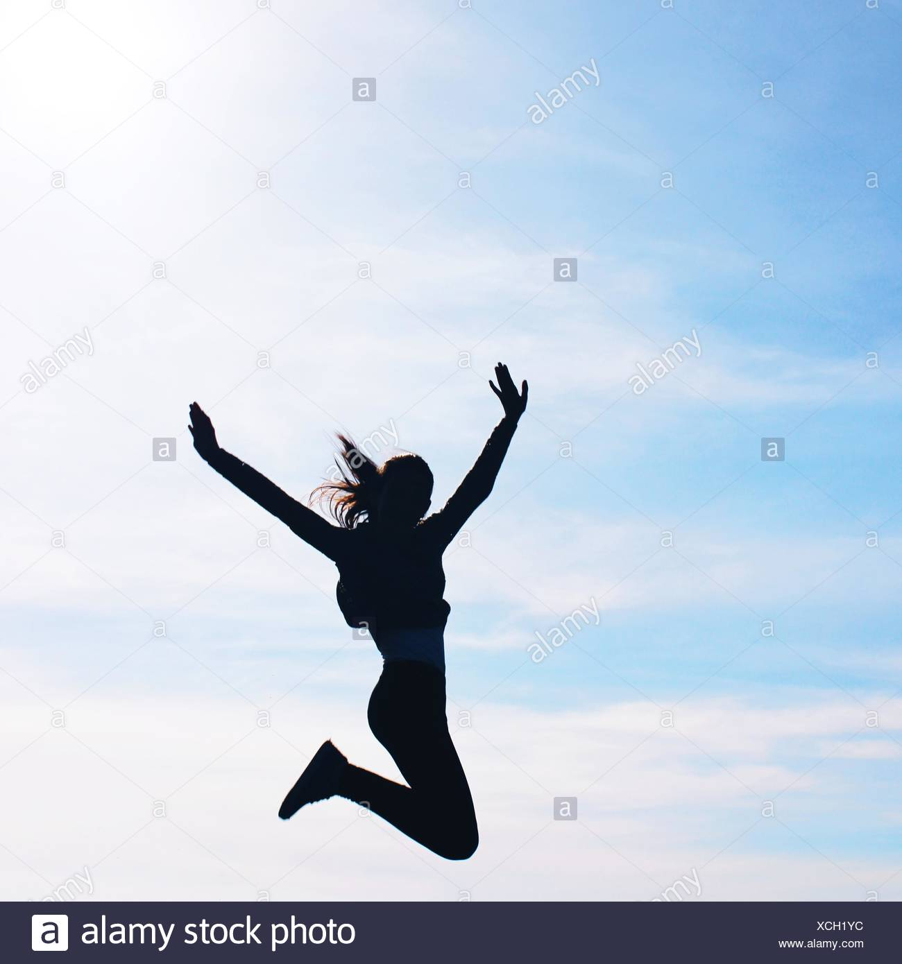 Silhouette of a girl jumping mid air - Stock Image