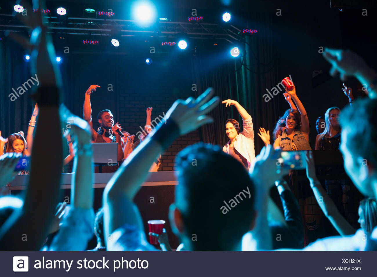 Crowd cheering for musical performers on stage - Stock Image
