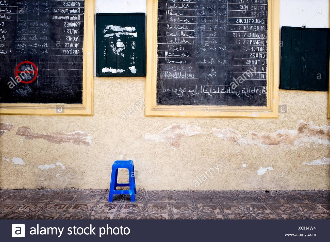 Wall at the entrance of a market with a blue stool and blackboards announcing prices of fruits and vegetables in French and Arab. Nouvelle Ville - Stock Image