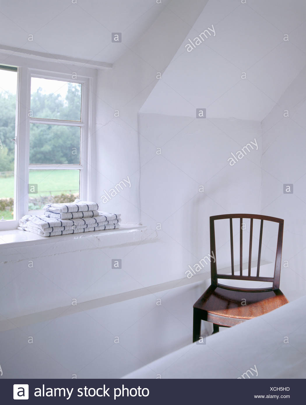 Wooden Chair Beside Open Window With Pile Of Towels On Windowsill In White Country Bedroom Sloping Ceiling