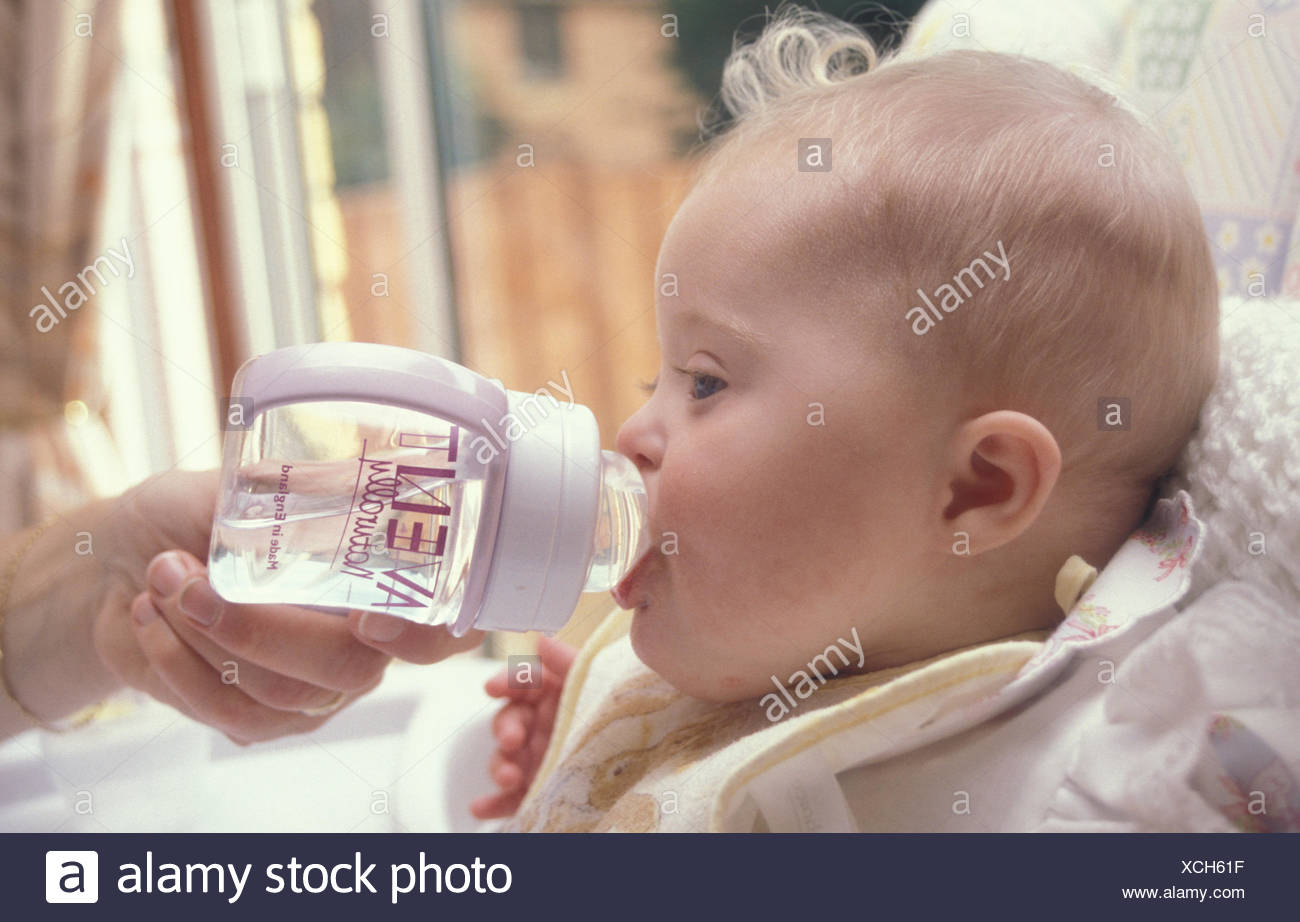 mother giving baby with Downs Syndrome bottle of water - Stock Image