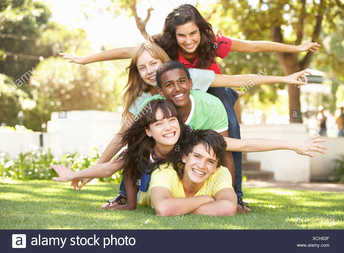 Group Of Teenagers Piled Up In Park - Stock Image