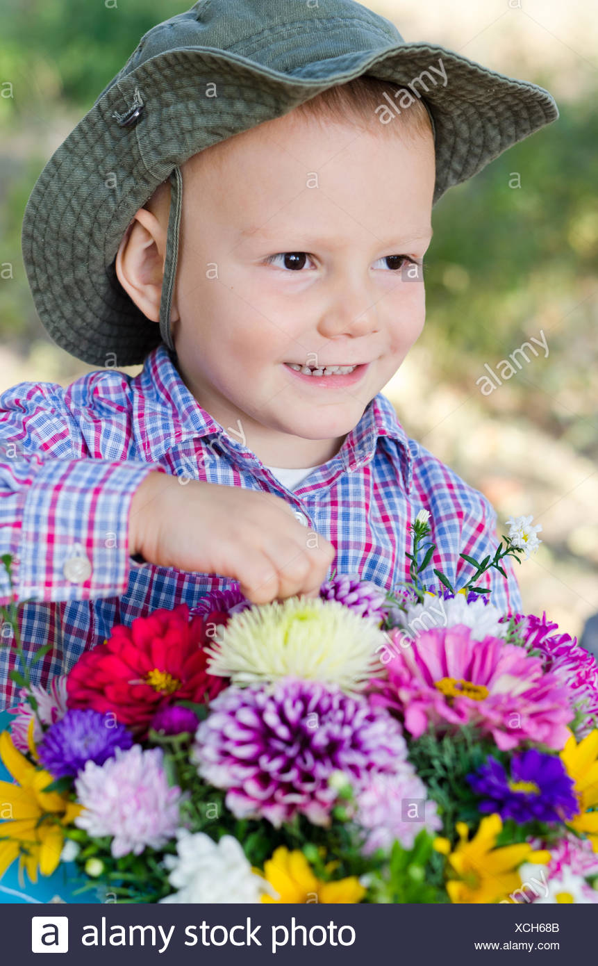Mischievous little boy with flowers - Stock Image