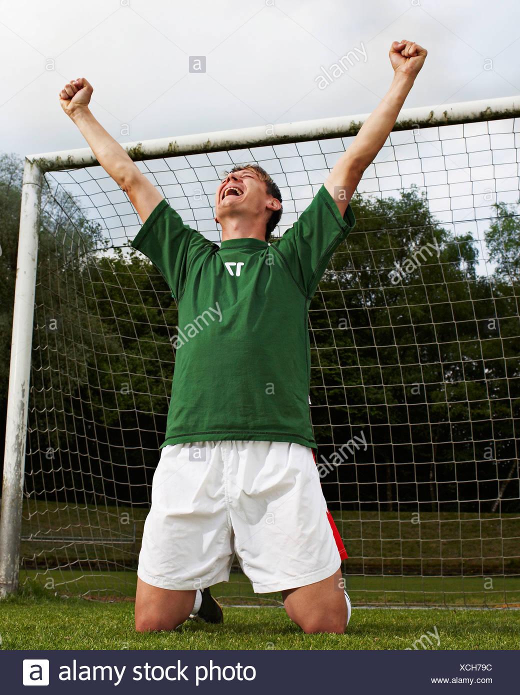 Soccer player celebrating on field - Stock Image
