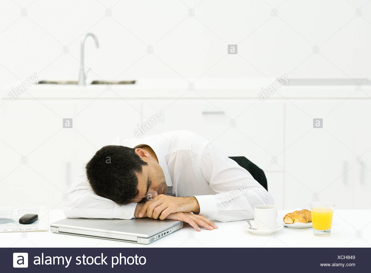 Businessman at breakfast table, resting head on laptop computer, eyes closed - Stock Image