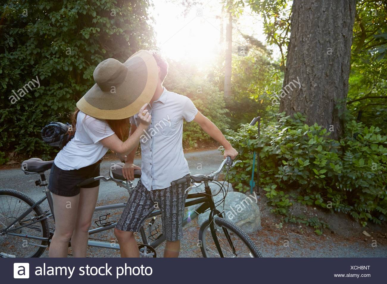 Young couple with tandem cycle kissing on rural road - Stock Image