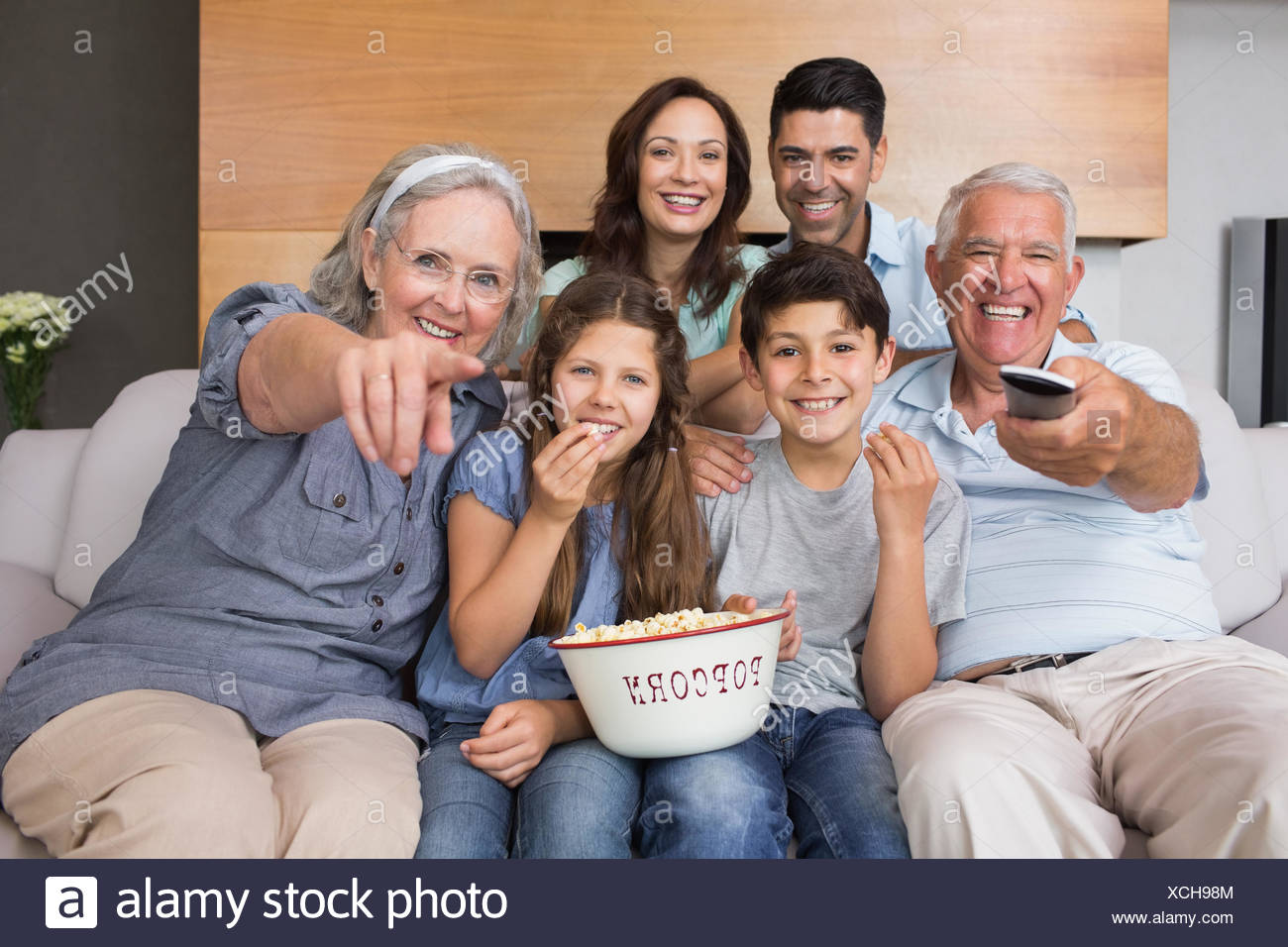 Portrait of happy extended family watching tv in living room - Stock Image